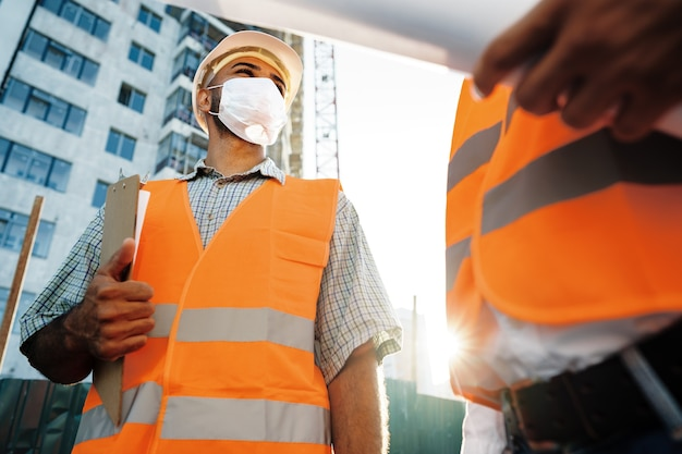 Zwei männer in arbeitskleidung und medizinischen masken, die mit blaupausen auf objekten arbeiten