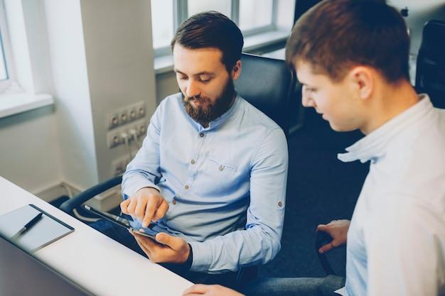 Zwei männer in eleganten hemden sitzen am schreibtisch und durchsuchen moderne tablette zusammen. männliche kollegen, die tablette zusammen verwenden
