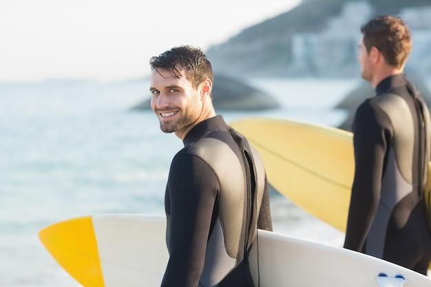 Zwei männer in wetsuits mit einem surfbrett an einem sonnigen tag