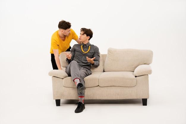 Zwei männer kommunizieren auf dem sofa sitzend