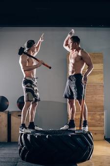 Zwei männer machen high five, während sie auf reifen stehen und einen vorschlaghammer halten