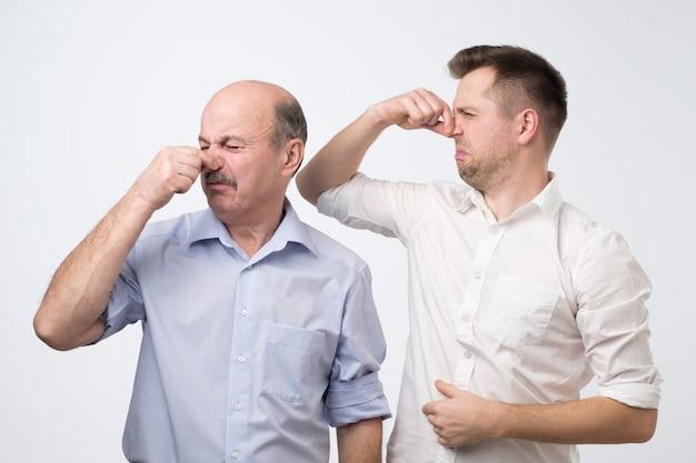 Zwei männer riechen etwas schreckliches