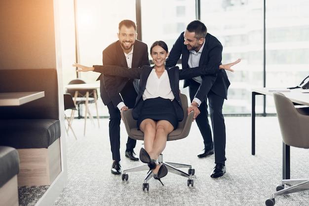 Zwei männer rollen ein mädchen auf einem stuhl im büro.