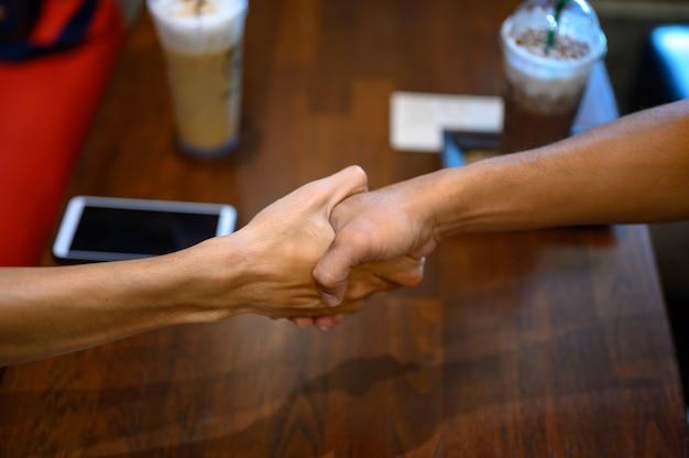 Zwei männer schließen sich den händen für die geschäftliche zusammenarbeit