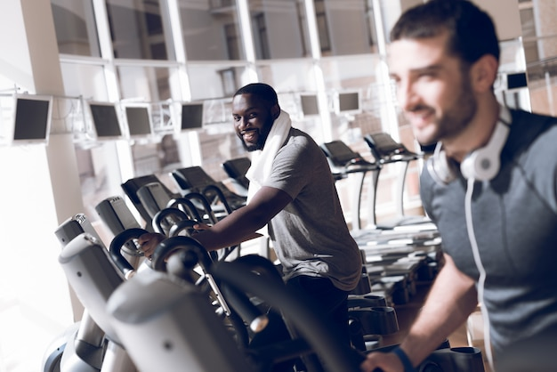 Zwei männer sind auf den laufbändern im modernen fitnessstudio beschäftigt