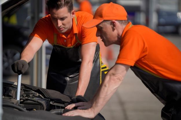 Zwei männer sind automechaniker überprüfen sie die autobatterie mit einem schraubenschlüssel und einer schnur.