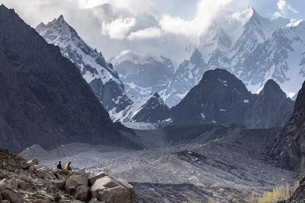 Zwei männer sitzen am rande der gletscherberge