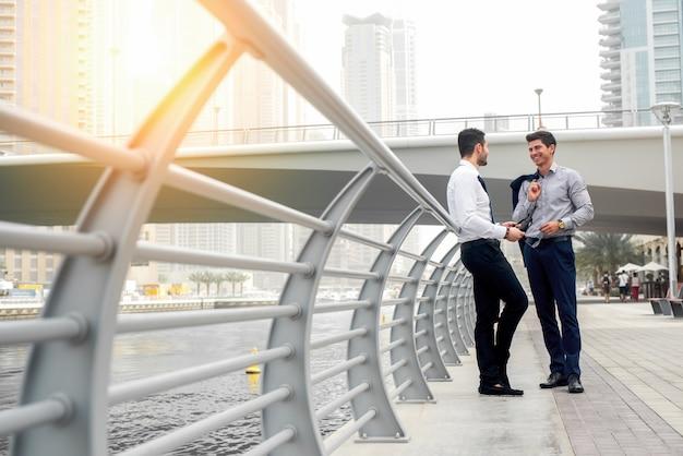 Zwei männer sprechen auf dem bürgersteig mit herrlichem blick auf die stadt