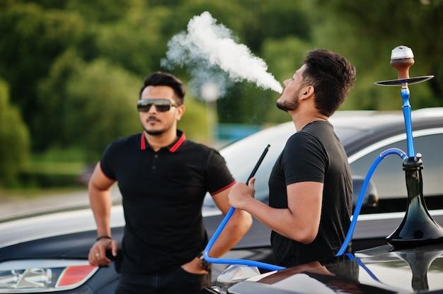 Zwei männer tragen ganz schwarz posierend in der nähe von geländewagen, die wasserpfeife rauchen