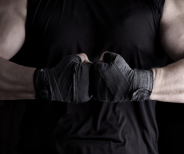 Zwei männerhände in einen schwarzen verband gewickelt