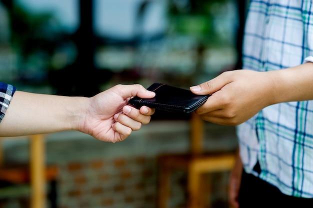 Zwei männerhände und geldbörse halten dieselbe geldbörse. sich gegenseitig beschenken das portemonnaie einsammeln und dem besitzer zurückgeben gute taten schaffen das eigene einkommen teilen