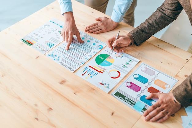Zwei männliche analysten oder ökonomen, die auf dokumente mit finanzinformationen zeigen, während sie diese auf einem arbeitstreffen diskutieren