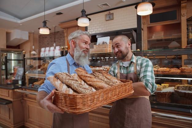 Zwei männliche bäcker vater und sohn verkaufen leckeres brot in ihrer bäckerei