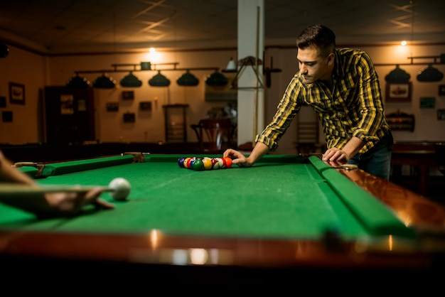 Zwei männliche billardspieler entspannen sich im poolraum. männer spielen amerikanisches poolspiel im sportverein