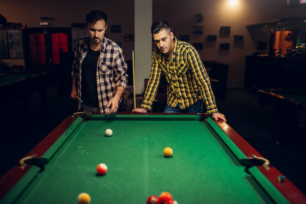 Zwei männliche billardspieler mit queue, poolraum