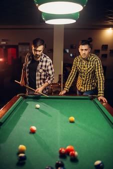 Zwei männliche billardspieler mit stichwort am tisch mit bunten bällen, poolraum. männer spielen amerikanisches poolspiel in der sportbar