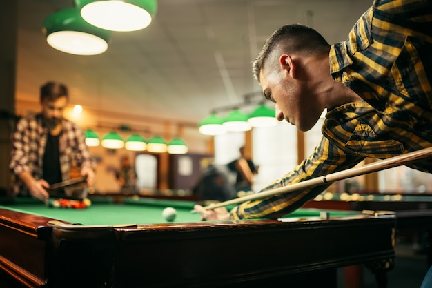 Zwei männliche billardspieler mit stichwort am tisch