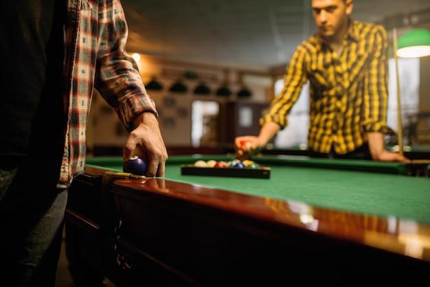 Zwei männliche billardspieler platzieren bunte bälle, poolraum. männer spielen amerikanisches poolspiel im sportverein