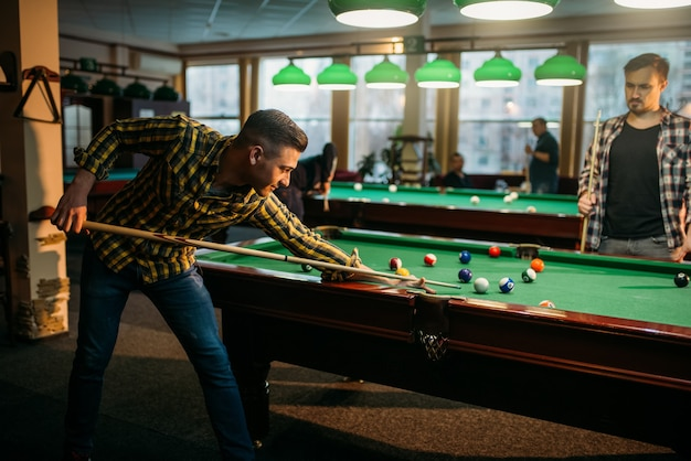 Zwei männliche billardspieler verbringen zeit im poolraum. männer spielen amerikanisches poolspiel im sportverein