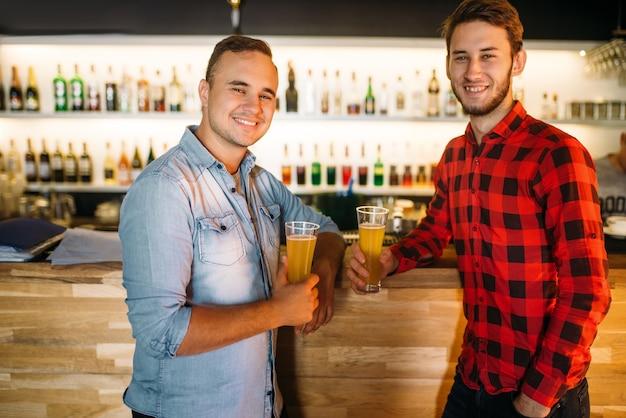 Zwei männliche bowler trinken frischen saft an der theke des bowlingclubs. die spieler entspannen sich nach dem wettkampf. aktive freizeit, gesunder lebensstil