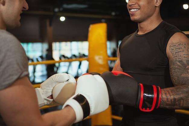 Zwei männliche boxer, die zusammen an der verpackenturnhalle ausarbeiten