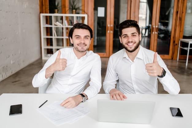 Zwei männliche büroangestellte zeigen daumen oben im büro