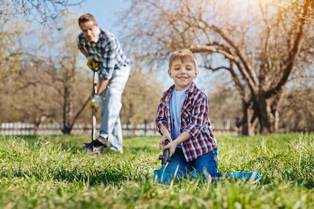 Zwei männliche familienmitglieder genießen die wochenenden im freien in einem garten, graben den boden und pflanzen die apfelbäume