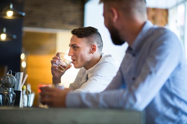 Zwei männliche freunde, die am barzähler genießt die getränke sitzen