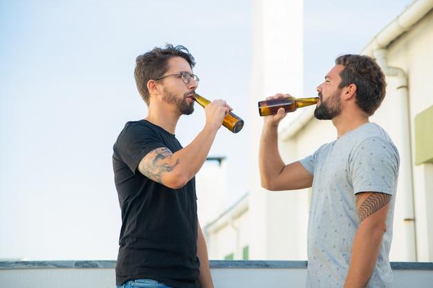 Zwei männliche freunde, die bier auf terrasse im freien genießen