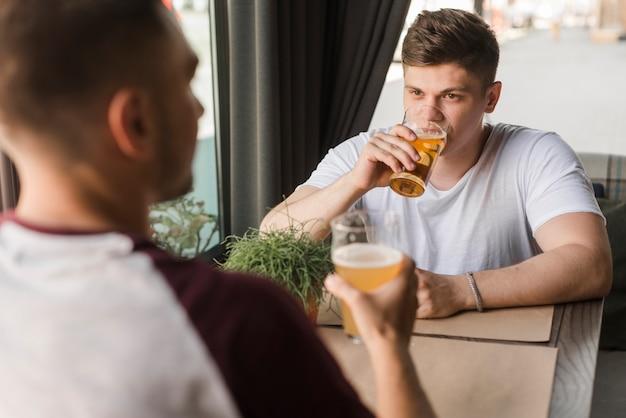 Zwei männliche freunde, die bier in den gläsern trinken