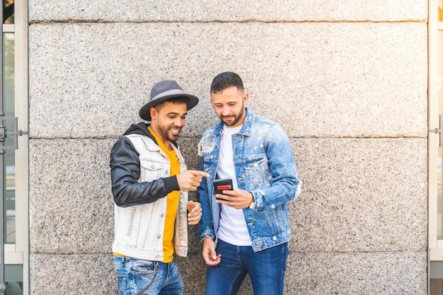 Zwei männliche freunde, die draußen handy beim lächeln verwenden.