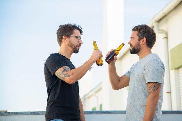 Zwei männliche freunde, die gute nachrichten teilen und bier trinken