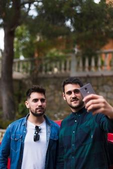 Zwei männliche freunde, die selfie am handy nehmen