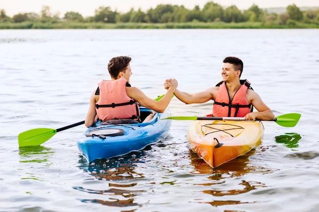 Zwei männliche freunde, die sich die hand beim kayak fahren auf see rütteln