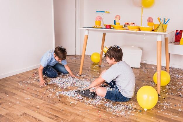 Zwei männliche freunde, die zu hause mit konfetti in der partei spielen