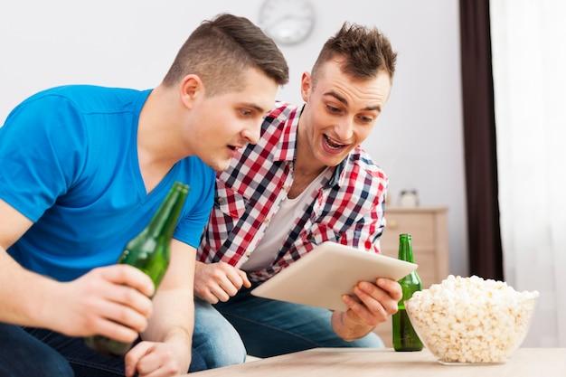 Zwei männliche freunde schockiert mit digitalem tablet
