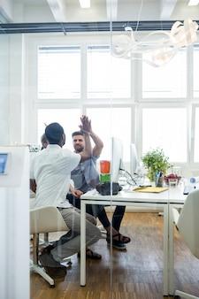 Zwei männliche grafiker geben high five zueinander