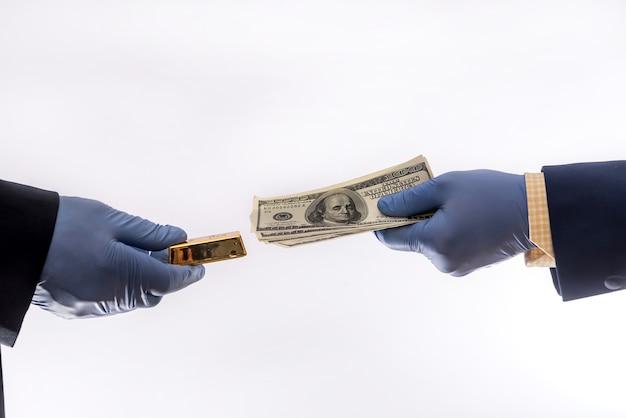 Zwei männliche hände in blauen medizinischen handschuhen mit 100-dollar-banknote, isoliert. konzept der korruption oder strahlung in quarantäne covid-19