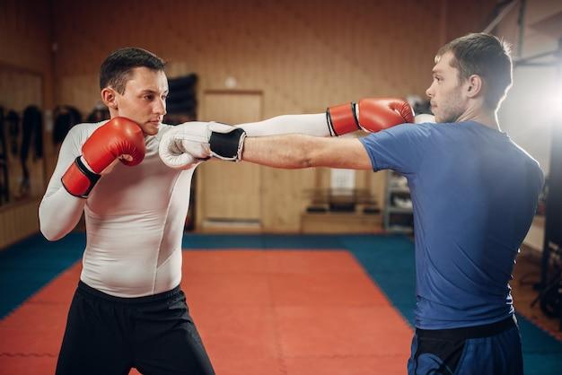 Zwei männliche kickboxer, die auf training im fitnessstudio üben