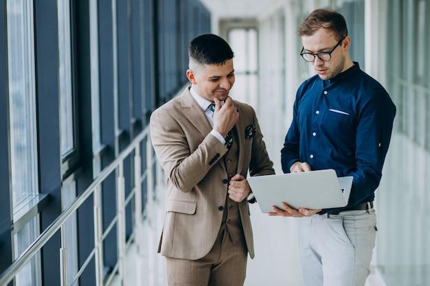 Zwei männliche kollegen im büro, stehend mit laptop