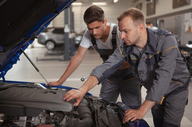 Zwei männliche mechaniker, die an der garage arbeiten