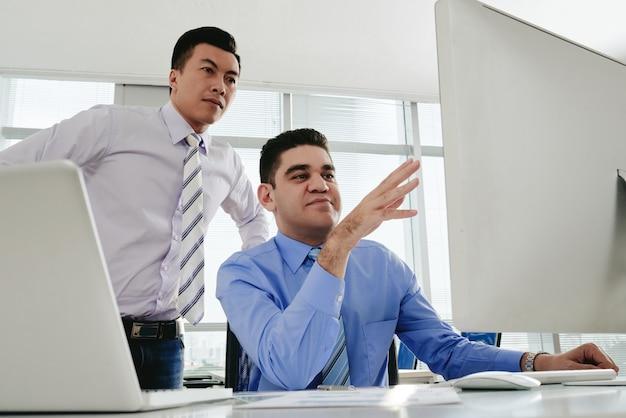 Zwei männliche mitarbeiter, die an einem projekt am bürocomputer zusammenarbeiten