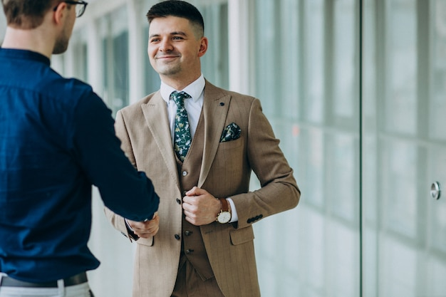 Zwei männliche partner, die hände im büro rütteln