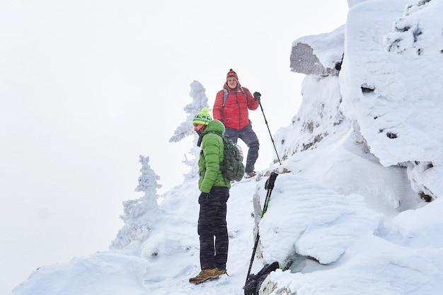 Zwei männliche reisende in den winterbergen zwischen den schneebedeckten klippen während eines schneesturms