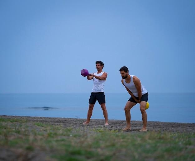 Zwei männliche sportler trainieren am strand mit kettlebells