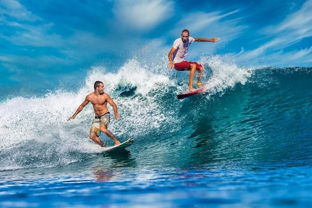 Zwei männliche surfer auf einer blauen welle am sonnigen tag