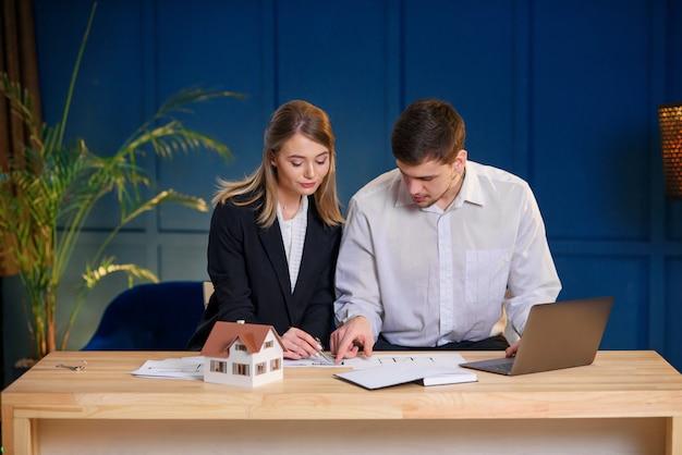 Zwei männliche und weibliche architekten diskutieren entwurf des neuen hauses, wohnung.
