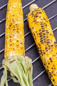 Zwei maiskolben gegrillter mais auf metallgrill. schwarzer hintergrund. ansicht von oben