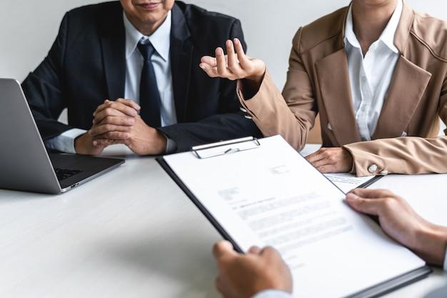 Zwei manager des auswahlausschusses stellen dem bewerber fragen zur arbeitserfahrung