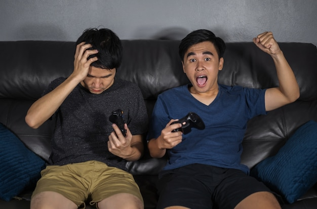Zwei-mann, der videospiele beim sitzen auf sofa spielt. gewinne und verliere emotionen
